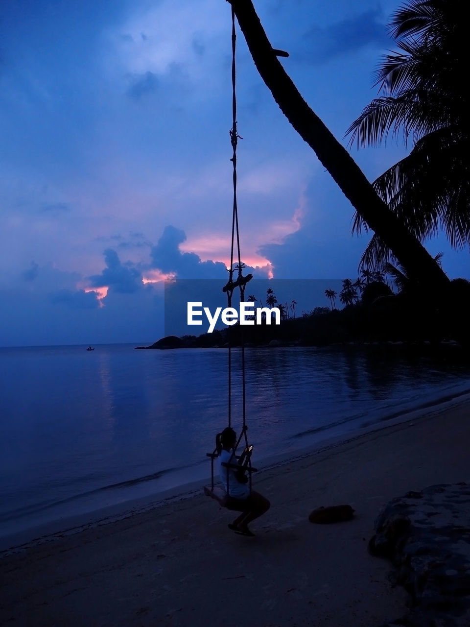 High Angle View Of Woman Using Phone While Sitting On Swing At Beach At Dusk