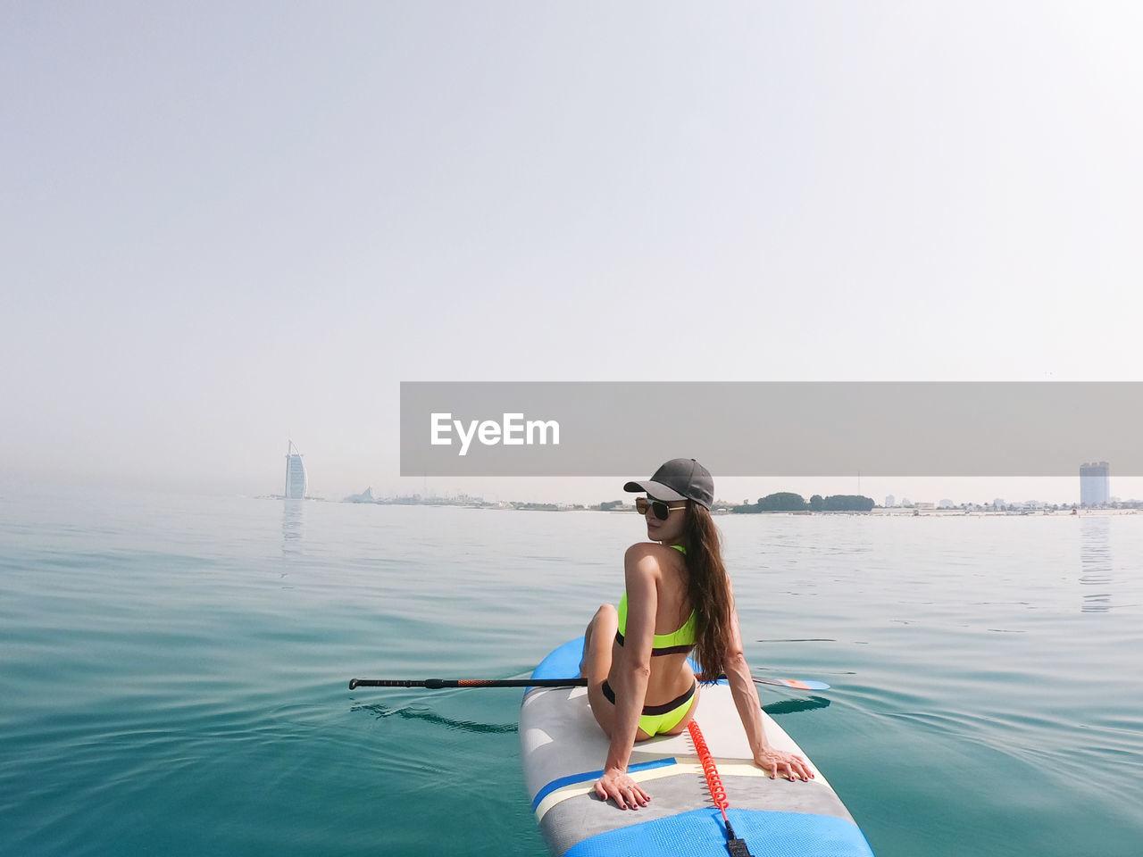 Young woman paddle boarding in dubai