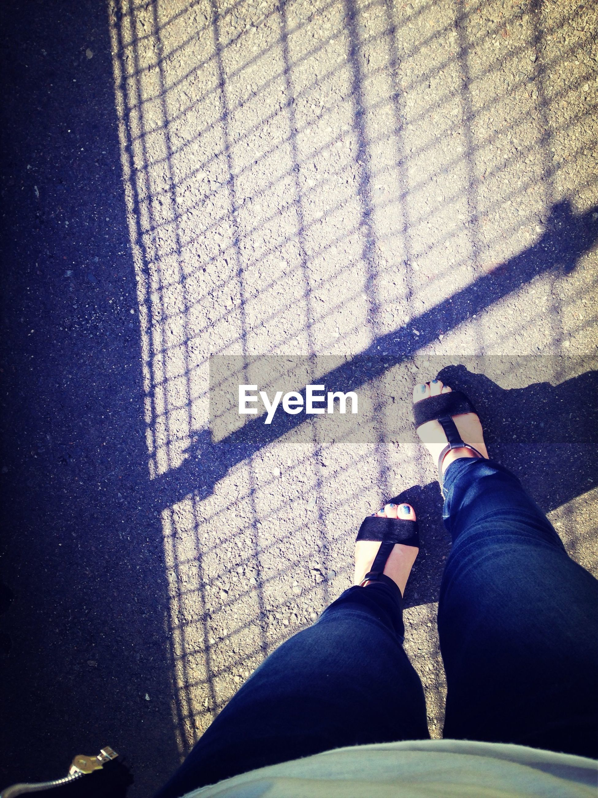 low section, person, personal perspective, lifestyles, shoe, human foot, high angle view, men, standing, leisure activity, footwear, shadow, jeans, street, sunlight, unrecognizable person