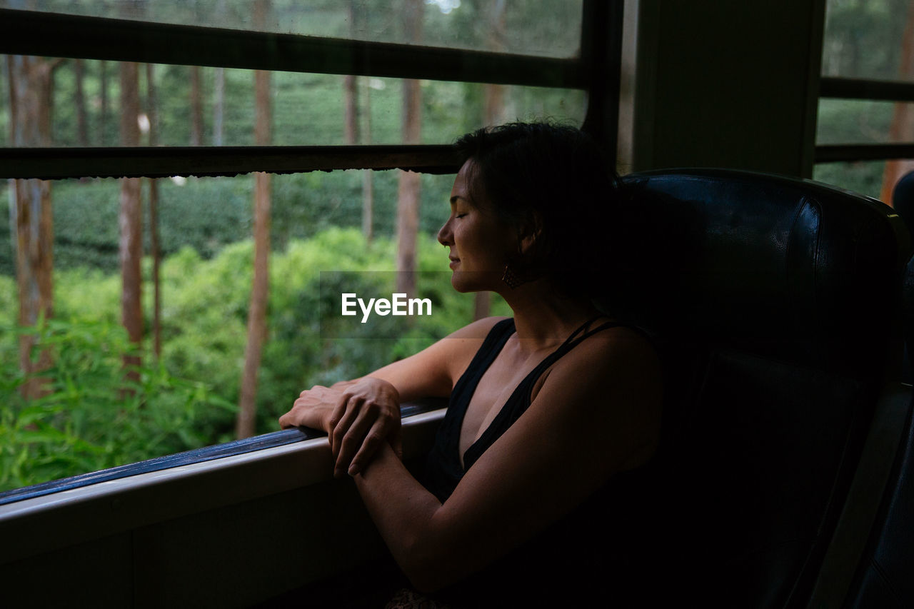 one person, window, real people, young adult, indoors, lifestyles, looking, glass - material, sitting, leisure activity, side view, young women, transparent, mode of transportation, looking through window, women, land vehicle, casual clothing, waist up, contemplation, profile view