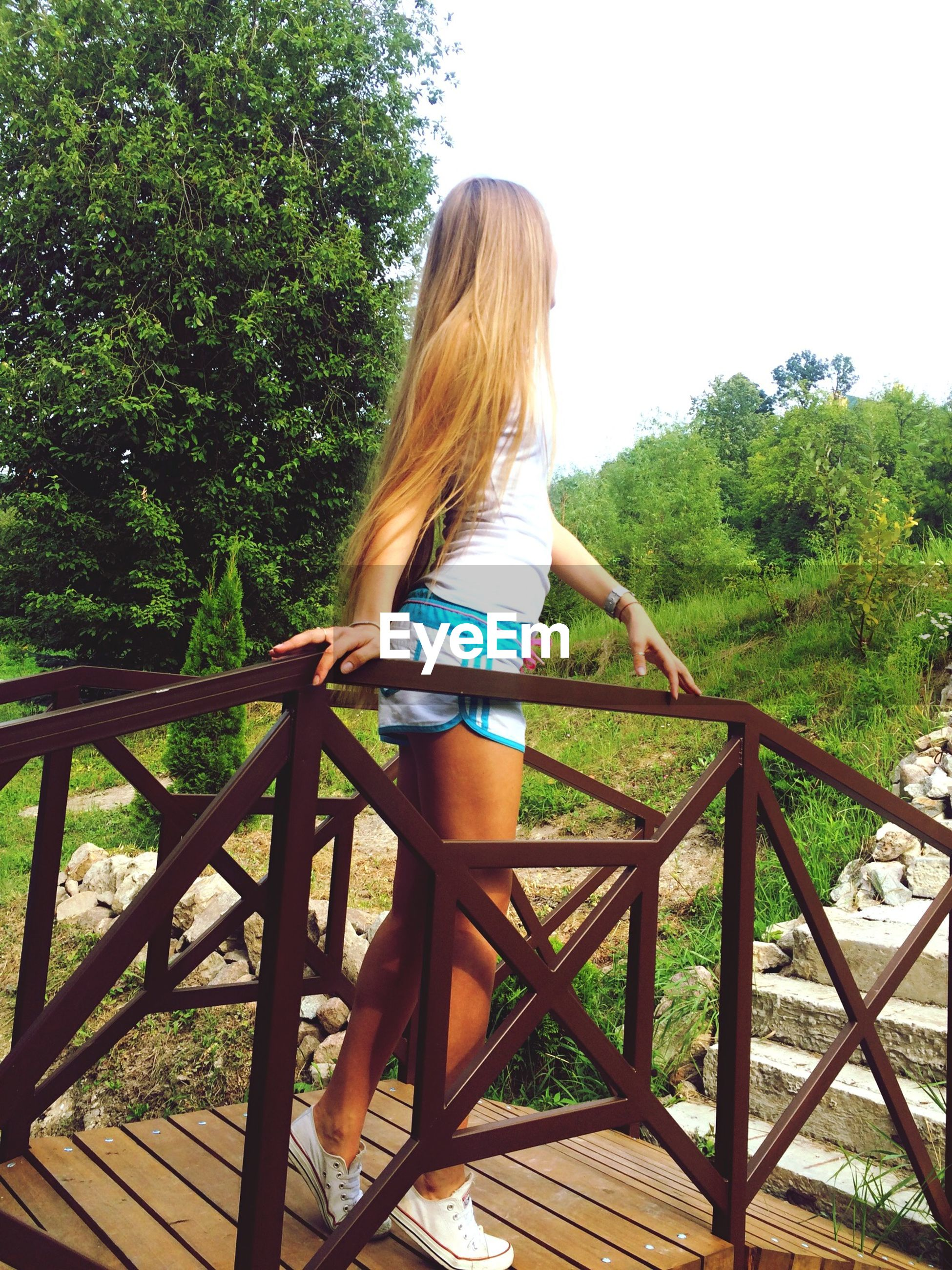 lifestyles, long hair, railing, leisure activity, casual clothing, person, young women, young adult, full length, standing, tree, blond hair, rear view, three quarter length, side view, day, waist up