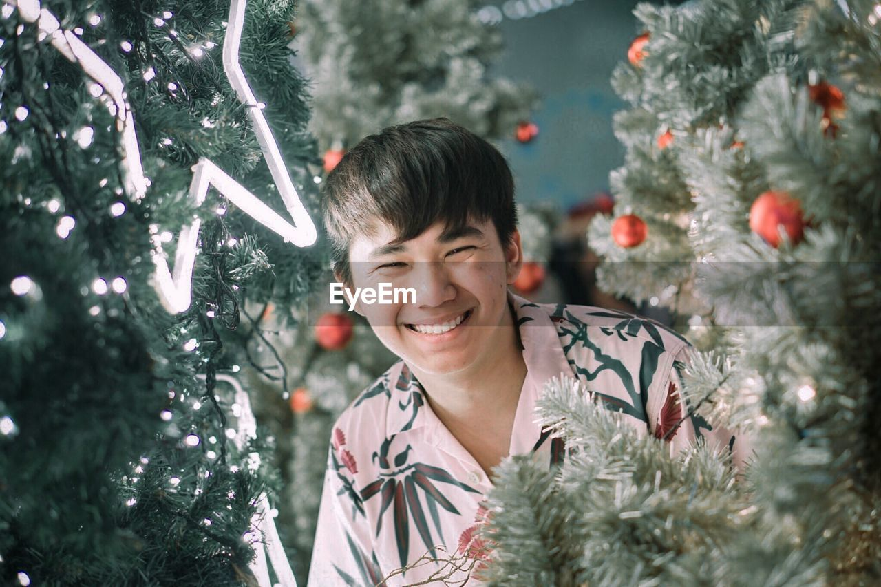Portrait Of Smiling Man Amidst Christmas Tree