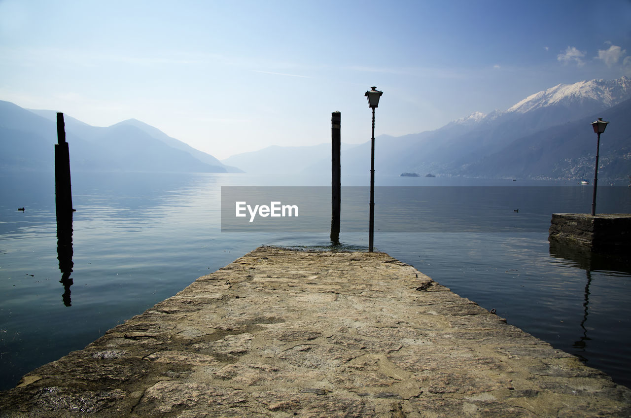 water, beauty in nature, scenics - nature, tranquil scene, mountain, sky, tranquility, lake, nature, no people, post, day, non-urban scene, street light, idyllic, outdoors, fog, cloud - sky, wooden post