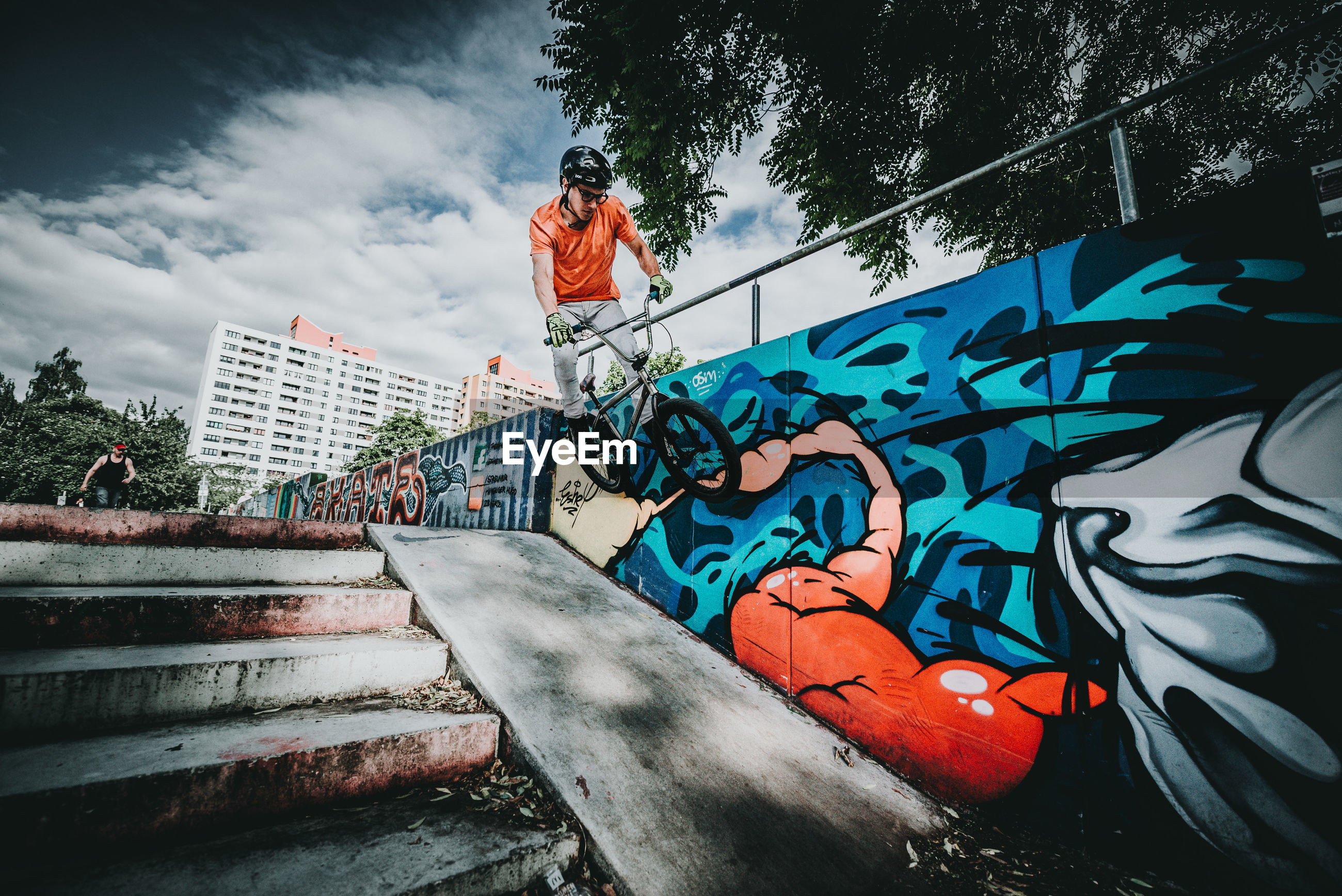 Man doing stunts with bicycle over steps by graffiti on wall
