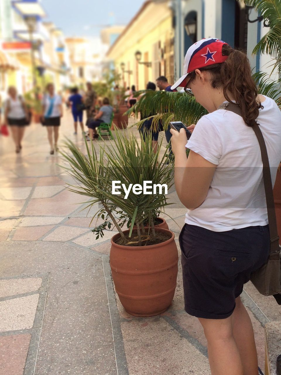 real people, casual clothing, day, one person, building exterior, potted plant, incidental people, outdoors, focus on foreground, growth, leisure activity, lifestyles, young adult, cap, plant, architecture, young women, standing, built structure, city