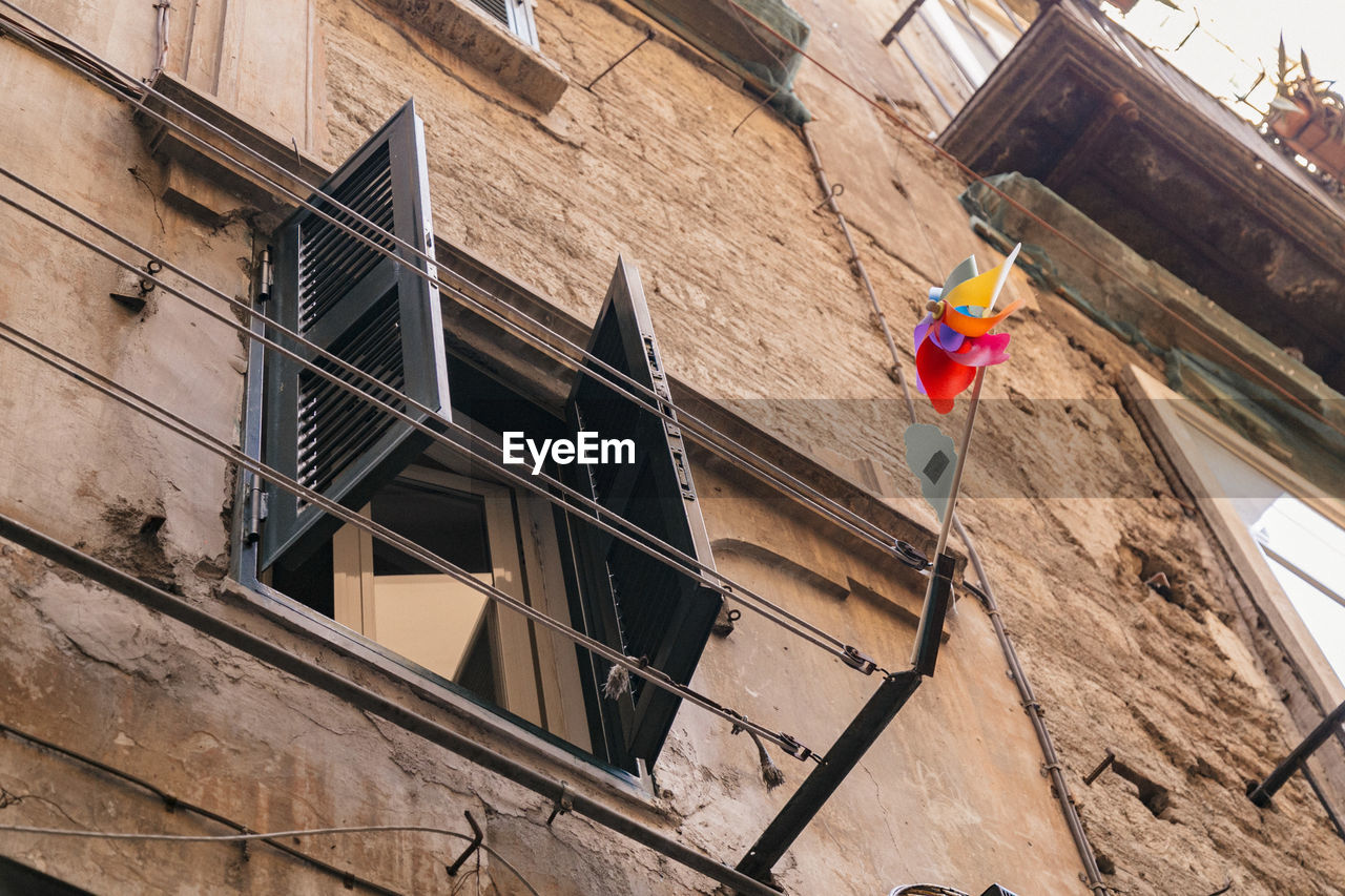 architecture, built structure, building exterior, low angle view, building, window, day, no people, flag, residential district, hanging, outdoors, wall, wall - building feature, city, nature, clothing, patriotism, balcony, apartment