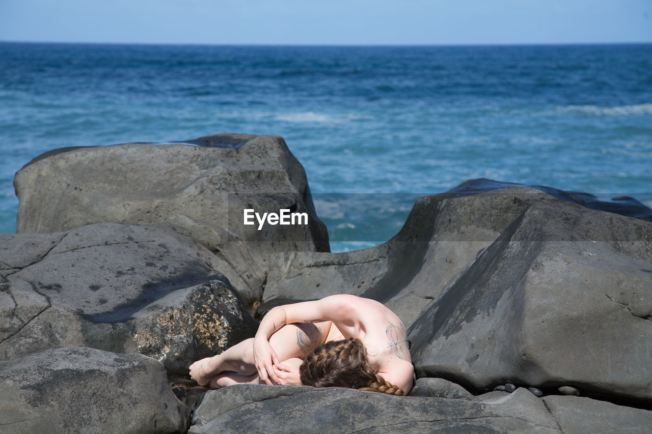 Naked Woman Lying On Rocky Shore
