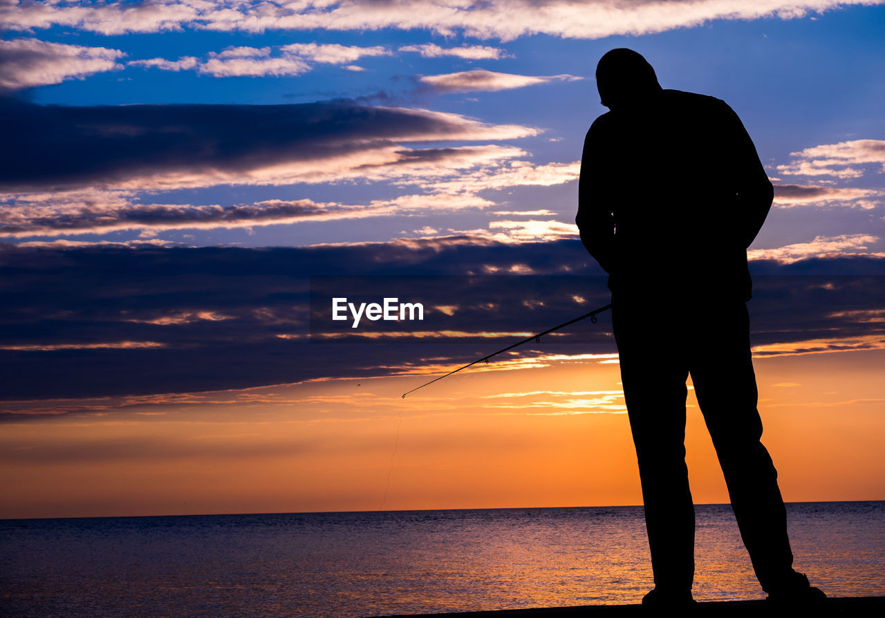 SILHOUETTE MAN STANDING ON SHORE AGAINST SEA DURING SUNSET