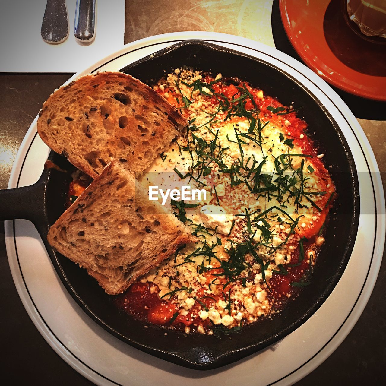 High angle view of shakshouka with breads in plate on table