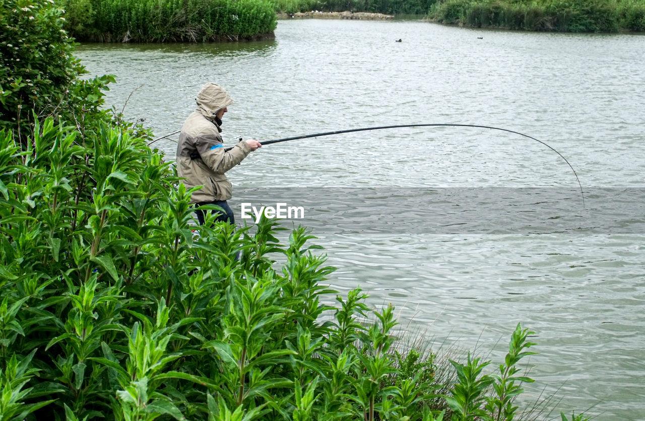Man fishing while standing by lake