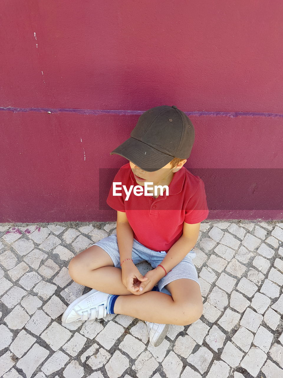 High angle view of boy wearing cap while sitting on footpath against wall