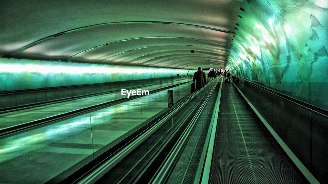 Rear View Of Man On Illuminated Moving Walkway