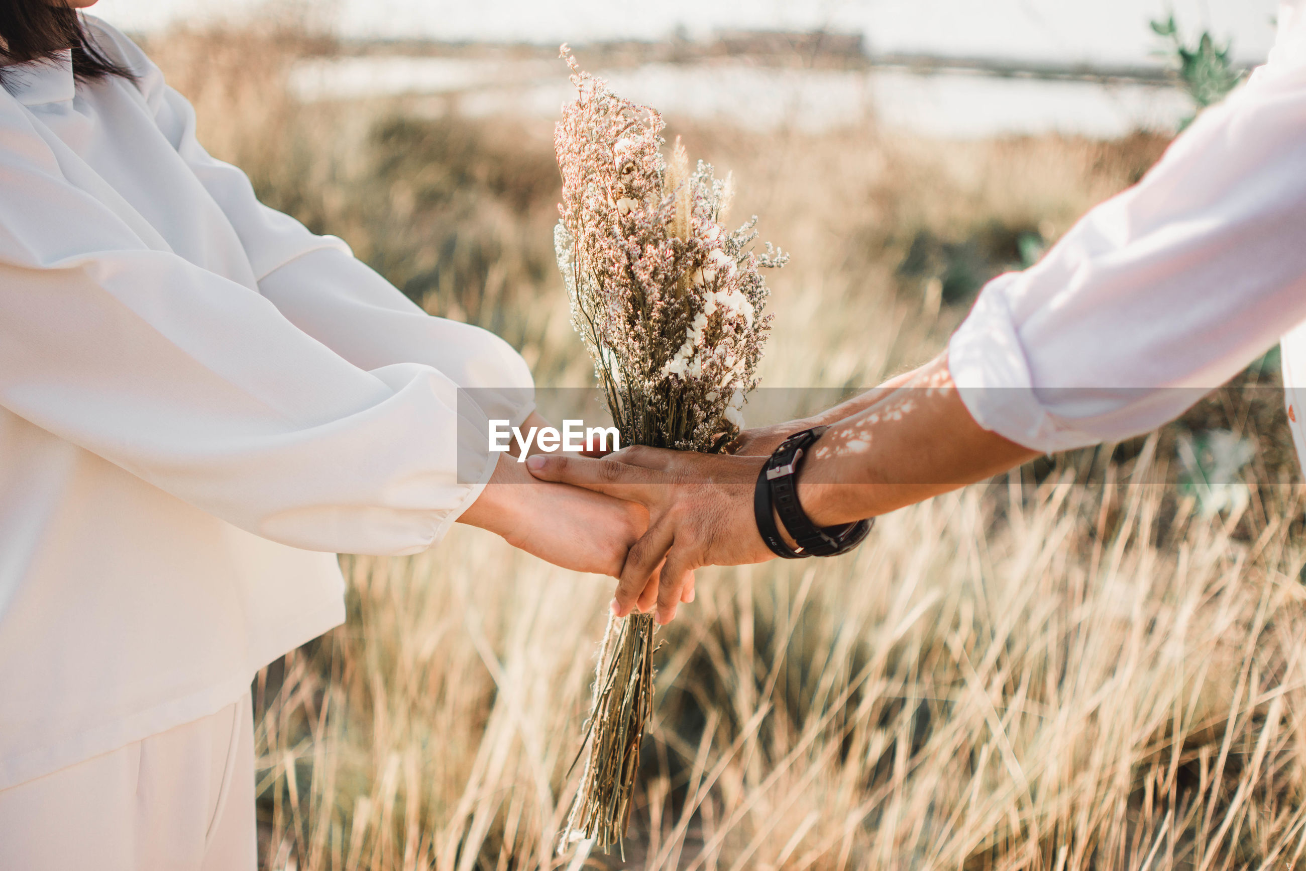 Wedding couple holding flowers while standing on grassy field