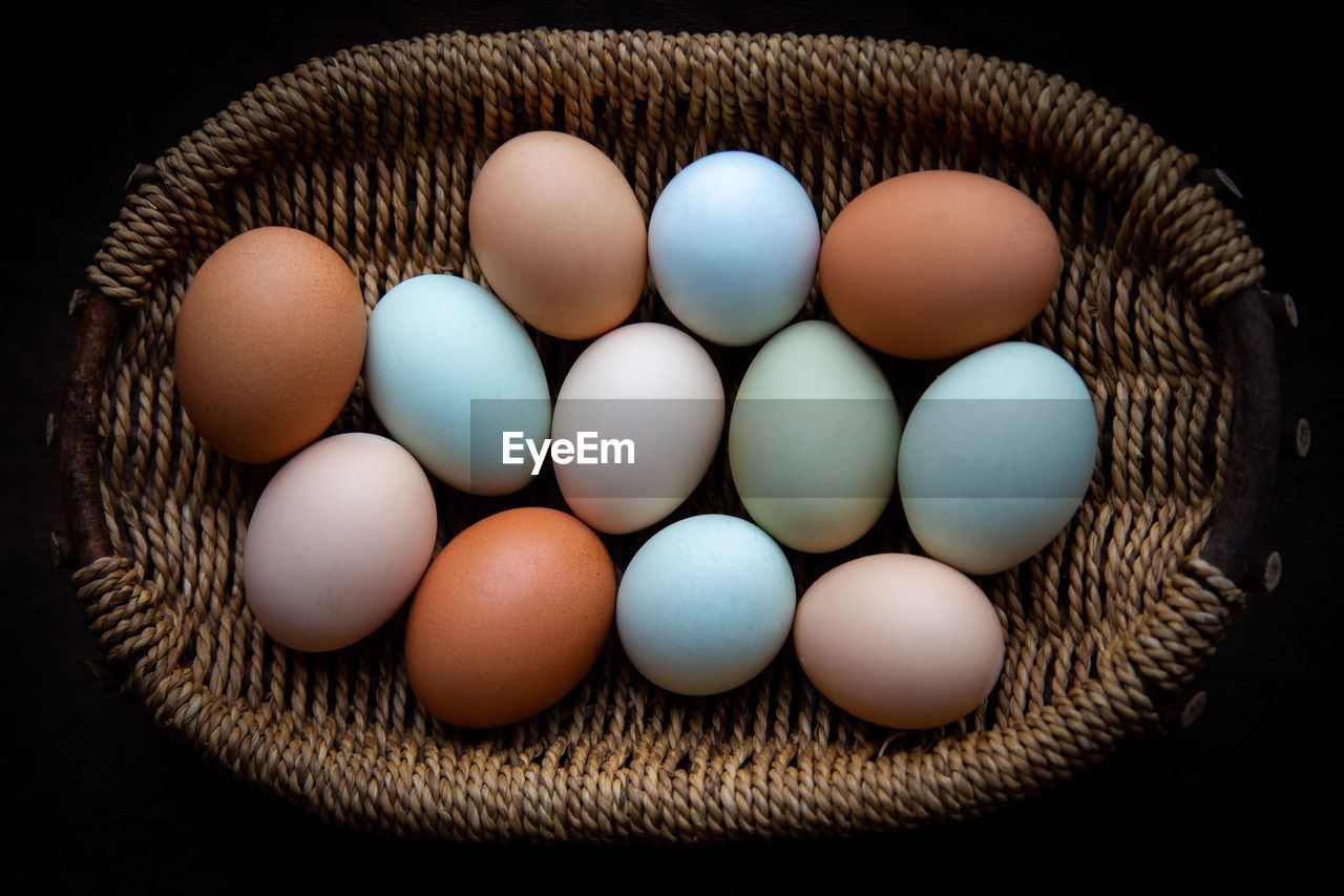 food, freshness, indoors, food and drink, wellbeing, still life, healthy eating, large group of objects, no people, high angle view, container, egg, close-up, vulnerability, basket, fragility, raw food, brown, directly above, black background