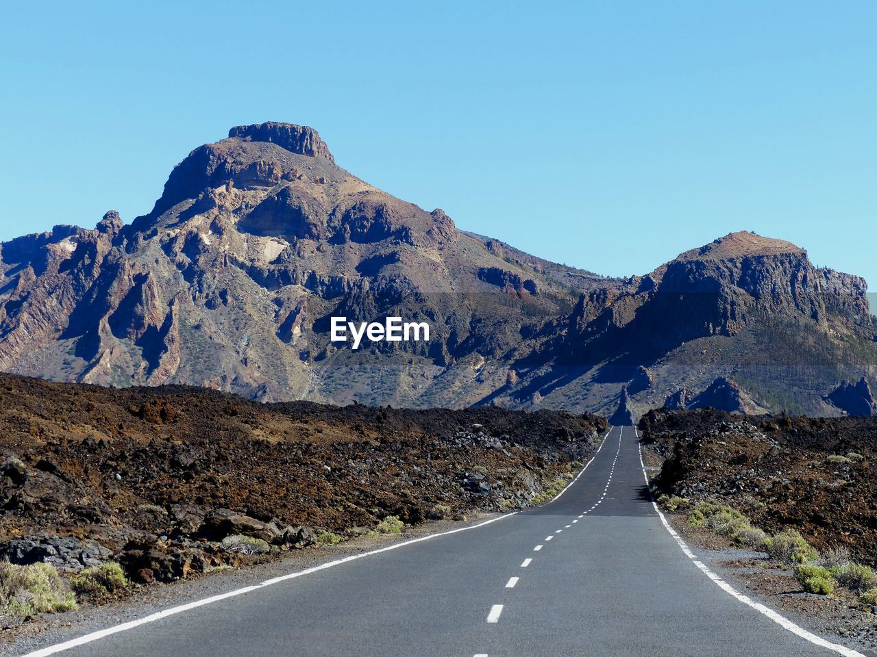 EMPTY ROAD AGAINST MOUNTAIN RANGE AGAINST CLEAR SKY