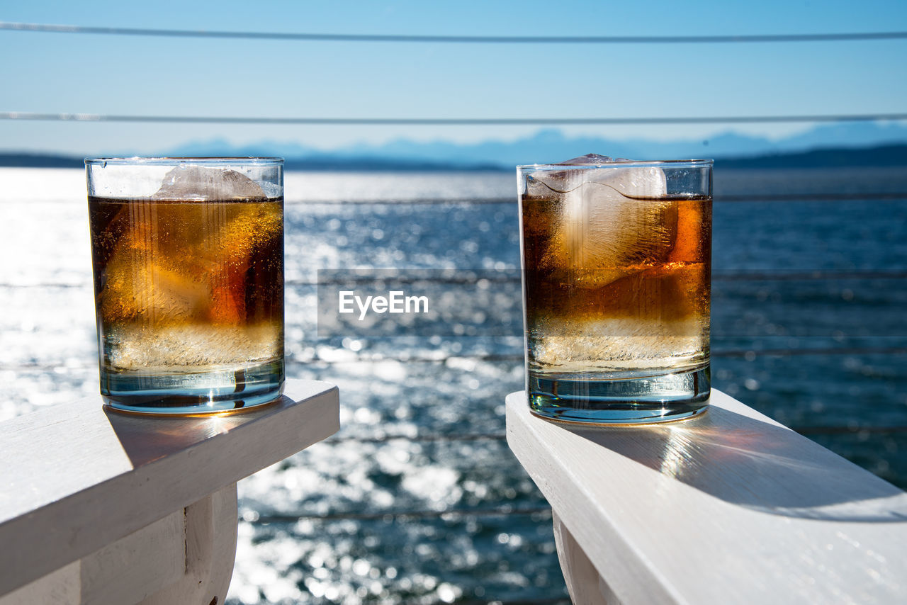Close-Up Of Whiskey Glass On White Armchair Against Sea