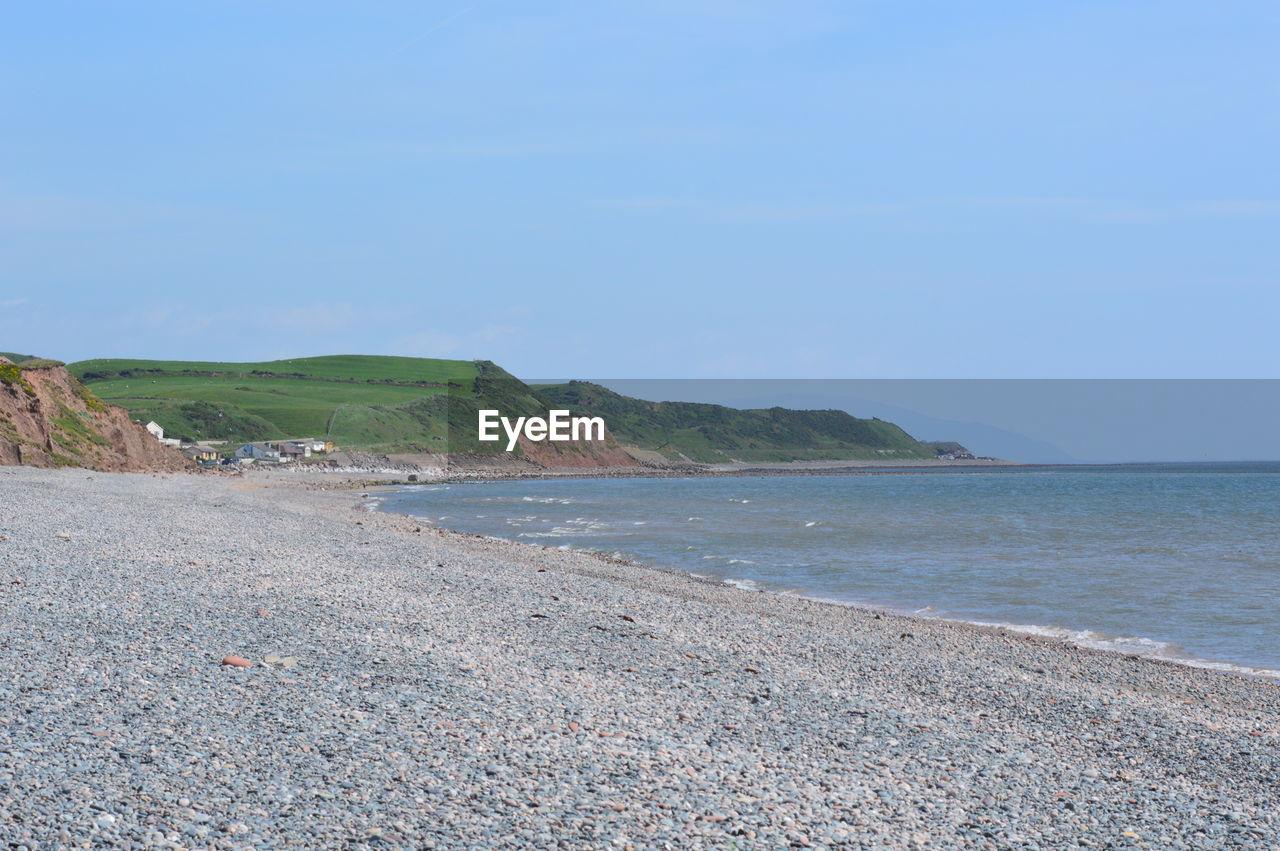 sea, water, sky, beauty in nature, land, tranquility, scenics - nature, tranquil scene, beach, day, nature, non-urban scene, no people, idyllic, copy space, mountain, horizon, outdoors, coastline, pebble