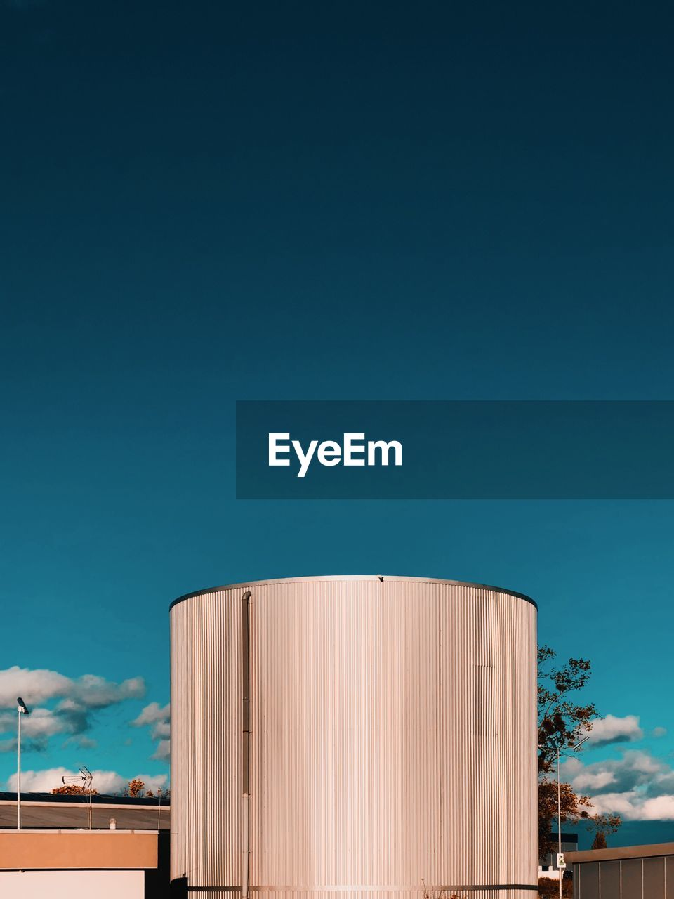 sky, architecture, built structure, copy space, building exterior, blue, industry, low angle view, nature, no people, clear sky, day, silo, factory, outdoors, storage compartment, storage tank, sunlight, fuel and power generation, corrugated