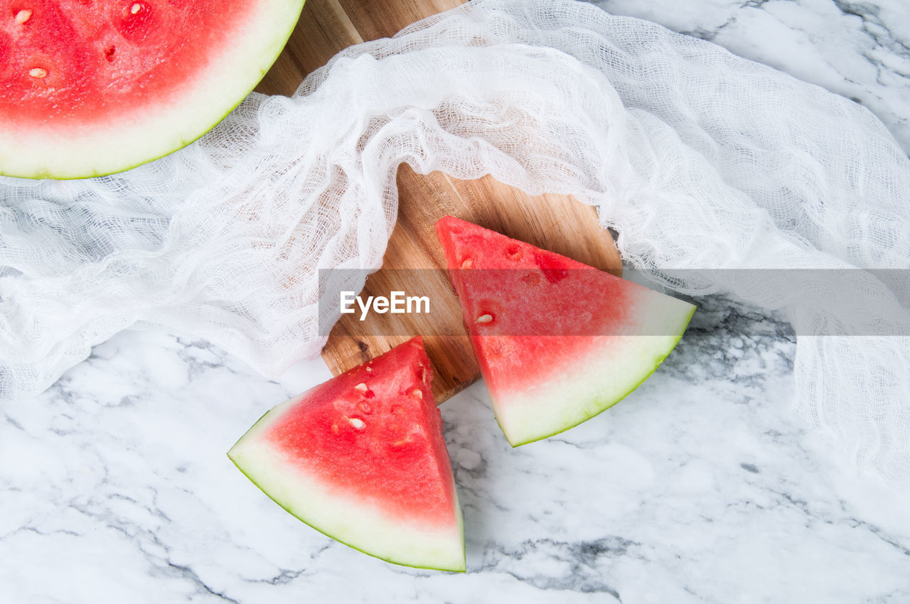 food, healthy eating, food and drink, watermelon, freshness, wellbeing, fruit, slice, no people, still life, high angle view, red, close-up, melon, indoors, juicy, cold temperature, table, healthy lifestyle, ripe
