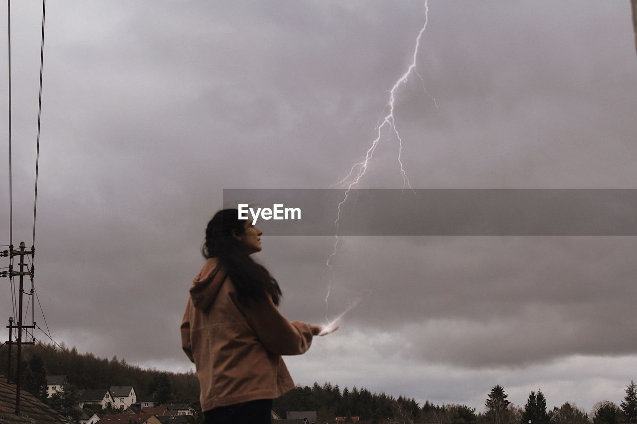 Side view of woman standing on field against lightning