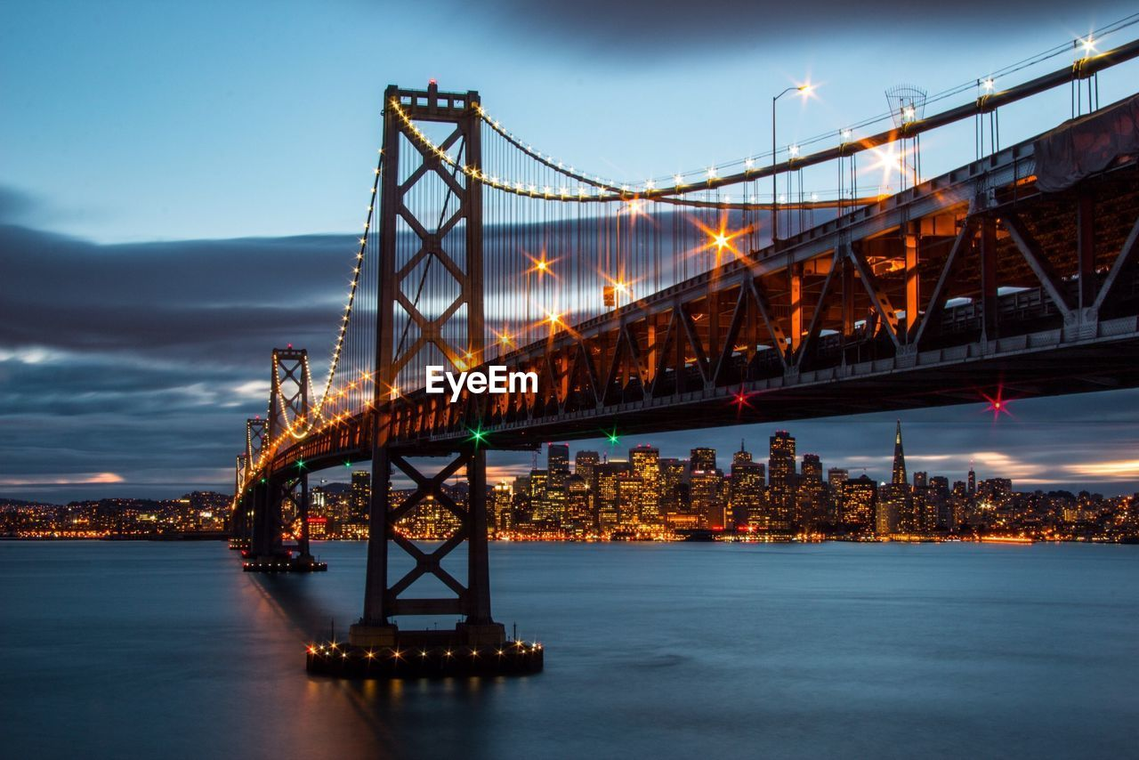 Illuminated suspension bridge with cityscape in background