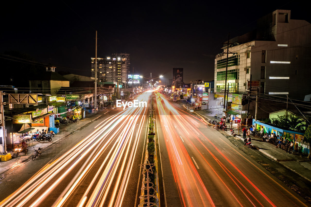 night, illuminated, light trail, long exposure, speed, motion, building exterior, architecture, built structure, blurred motion, street, transportation, city, high street, road, traffic, outdoors, high angle view, city life, urban scene, no people, sky