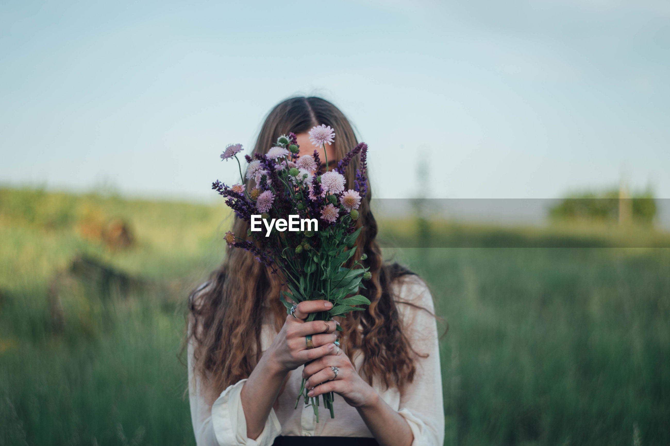 Young woman covering face with flowers while standing on land