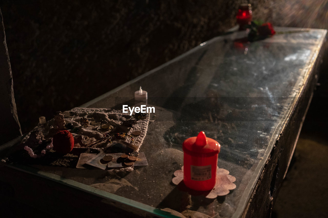 no people, red, burning, high angle view, indoors, ash, close-up, container, burnt, focus on foreground, social issues, day, nature, cigarette, table, candle, still life, food and drink, box, messy