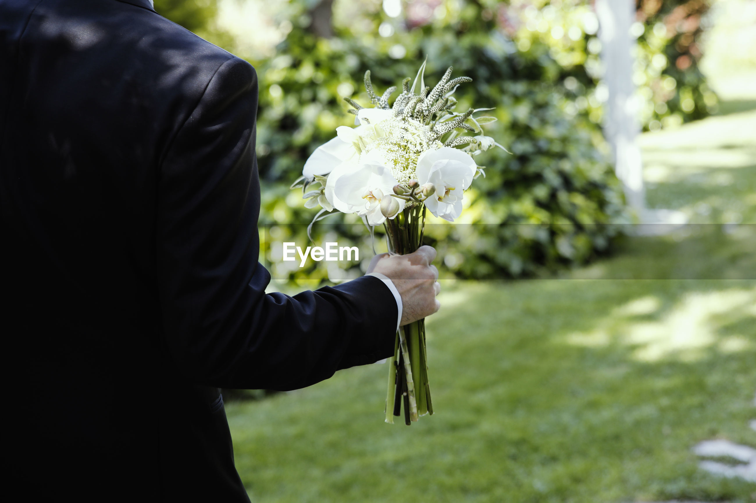 Midsection of bridegroom holding white flowers at park
