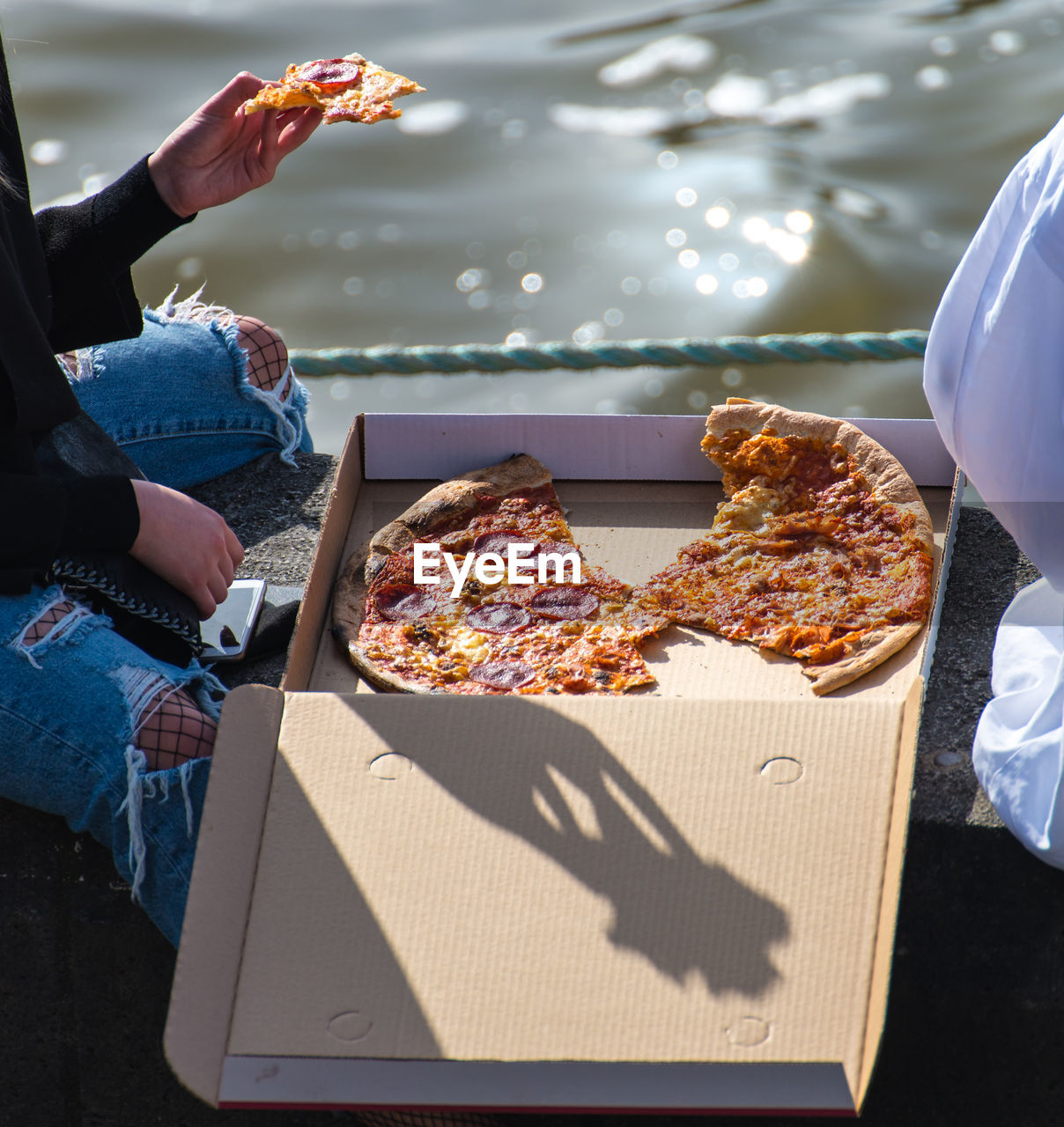 Close-Up Of People Eating Pizza By Water