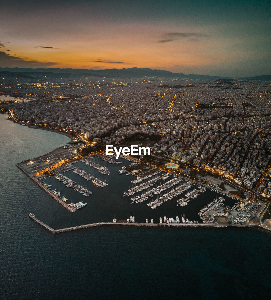 Aerial View Of Sea Against Cityscape During Sunset