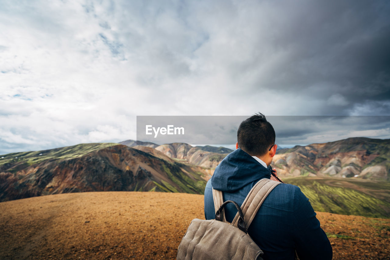 Rear View Of Hiker Looking At Mountains Against Cloudy Sky