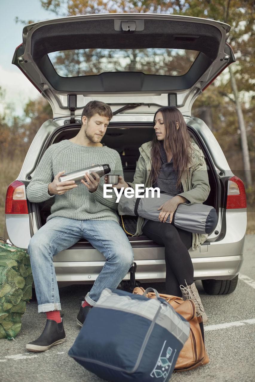 FULL LENGTH OF COUPLE SITTING ON CAR