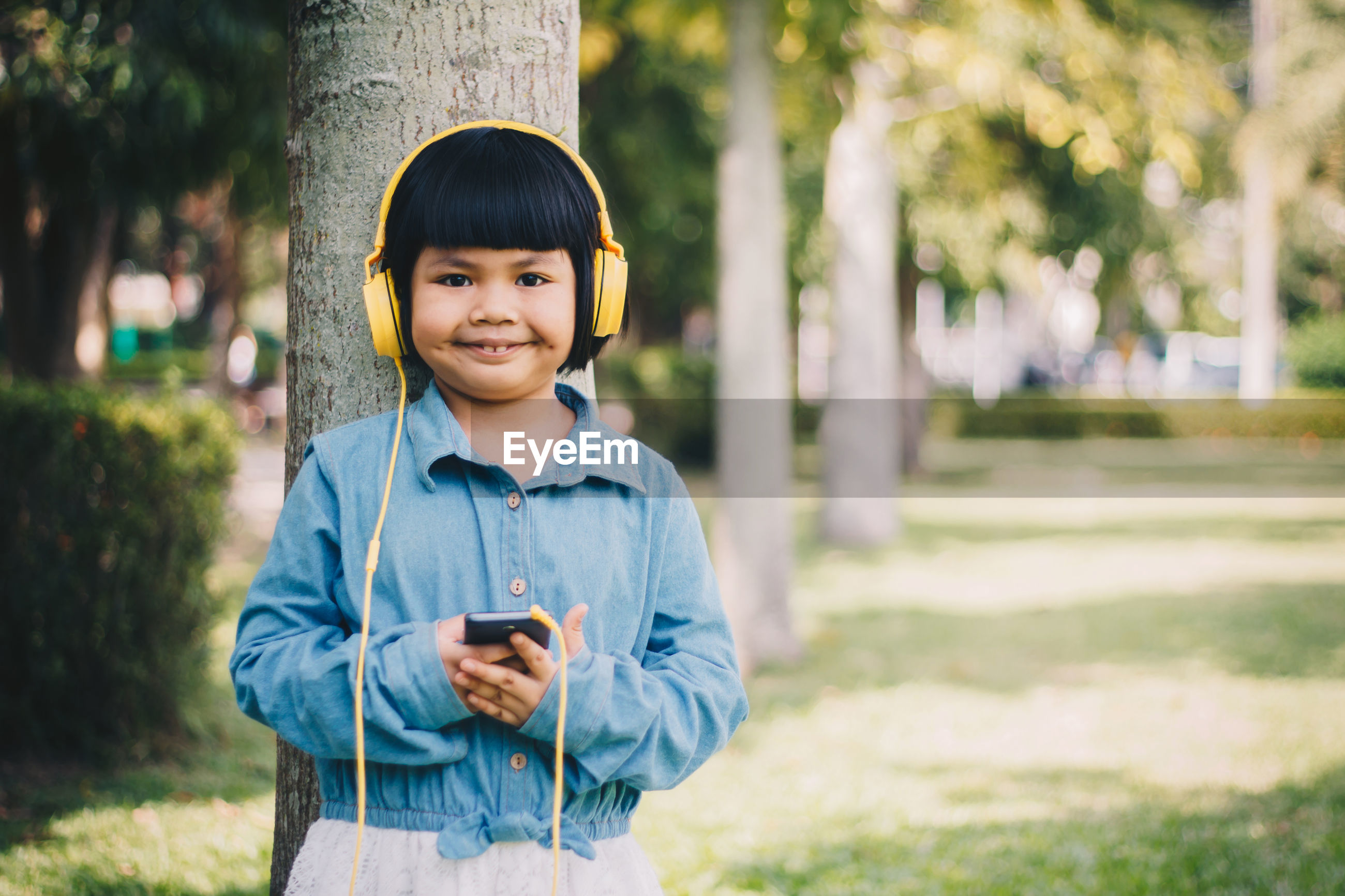 Portrait of smiling girl listening music on mobile phone while standing against tree trunk