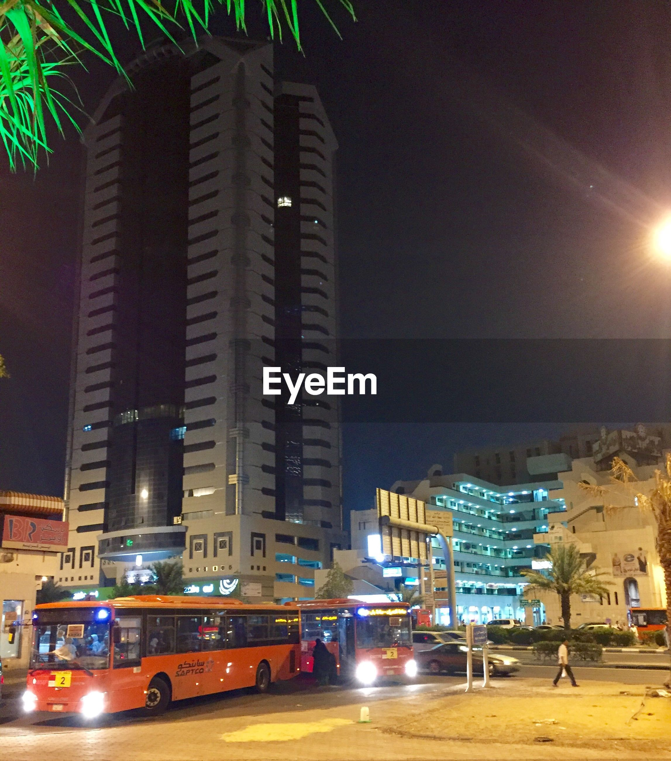 building exterior, architecture, city, built structure, illuminated, tall - high, office building, night, transportation, road, skyscraper, tower, city life, tall, city street, mode of transport, modern, building story, sky, growth, outdoors, development