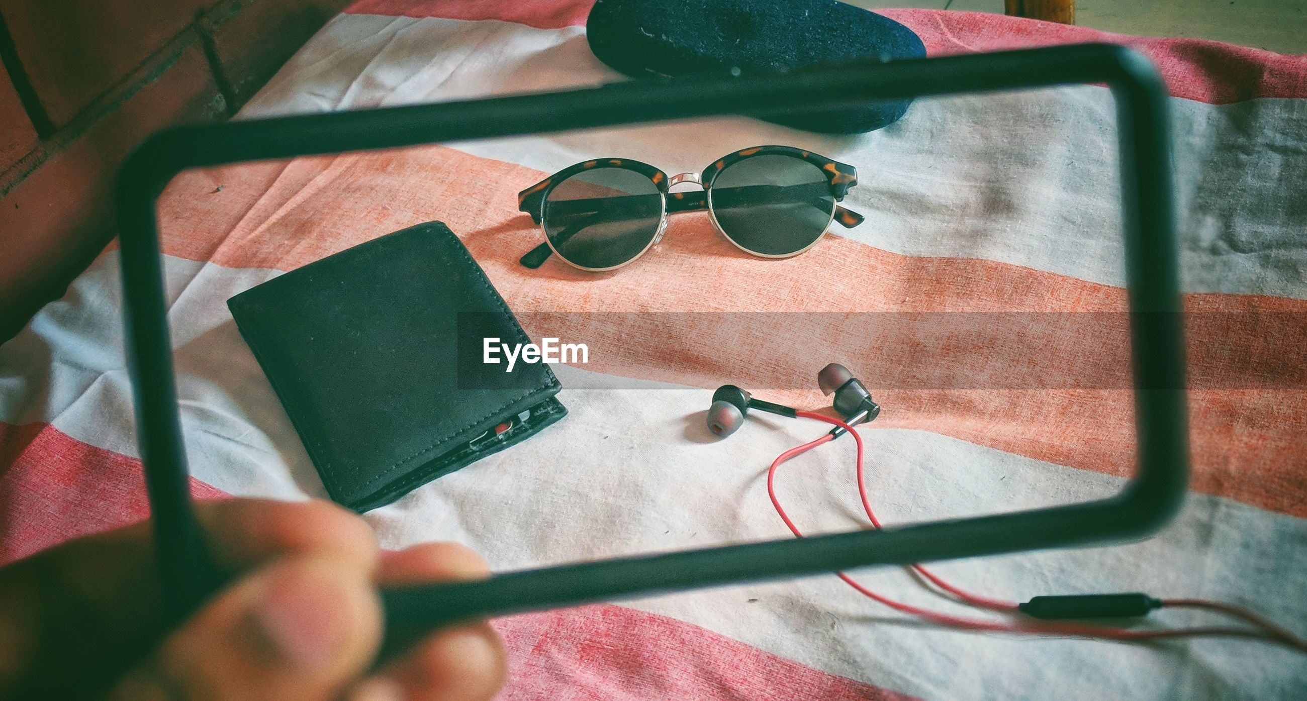 Cropped hand holding frame against purse with sunglasses and in-ear headphones on table