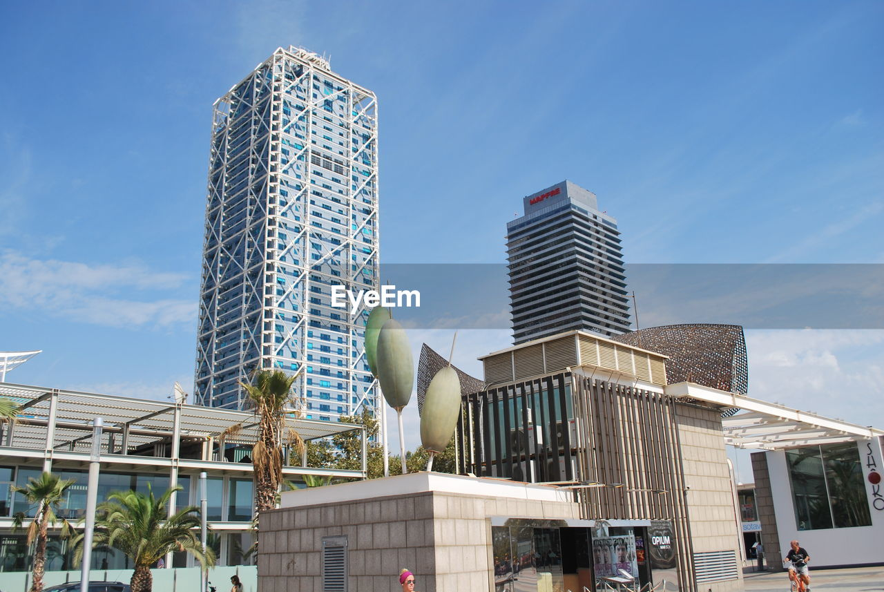 architecture, modern, building exterior, built structure, skyscraper, city, low angle view, day, sky, travel destinations, outdoors, urban skyline, tree, no people, office park