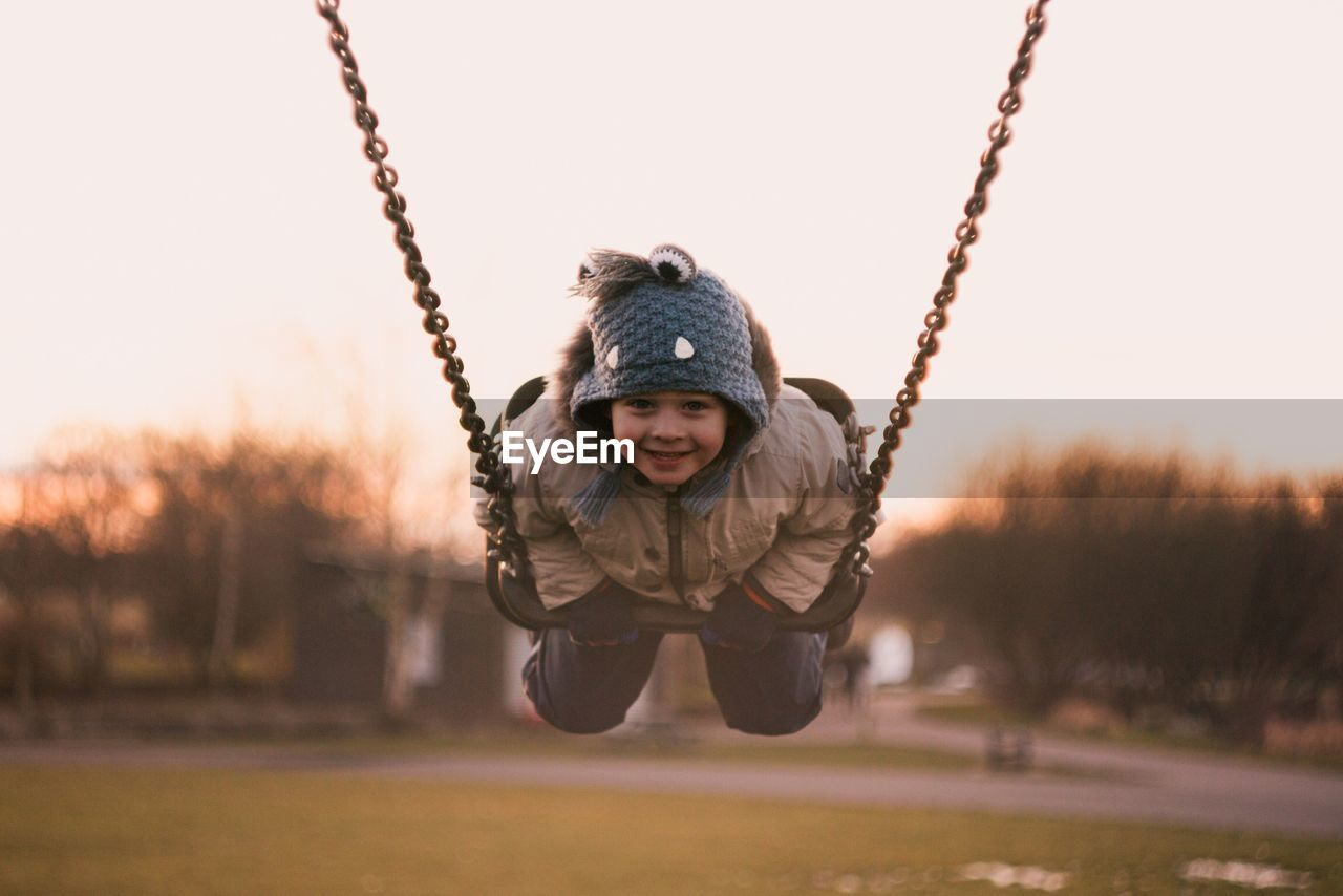 childhood, one person, child, full length, leisure activity, swing, playground, boys, real people, nature, casual clothing, front view, men, focus on foreground, males, warm clothing, enjoyment, portrait, sunset, looking at camera, outdoors, innocence