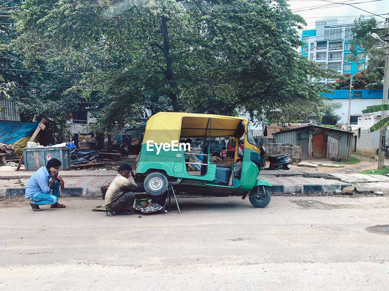 tree, transportation, plant, men, city, building exterior, real people, mode of transportation, built structure, architecture, day, group of people, land vehicle, sitting, street, nature, people, incidental people, building, outdoors