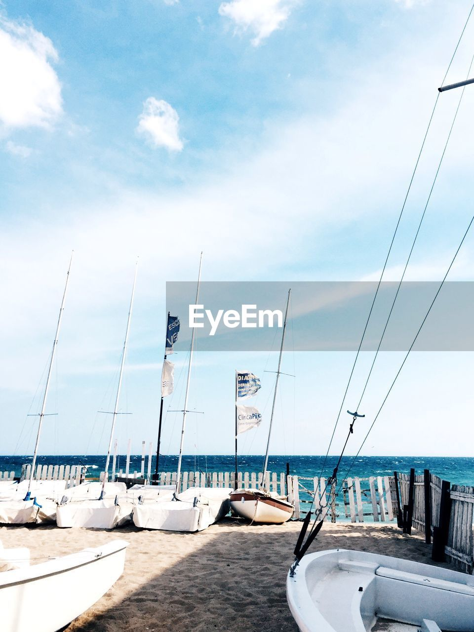 sea, water, sky, cloud - sky, nature, nautical vessel, day, flag, scenics, tranquil scene, no people, outdoors, beauty in nature, tranquility, sunlight, horizon over water, beach, sailboat, mast, yacht