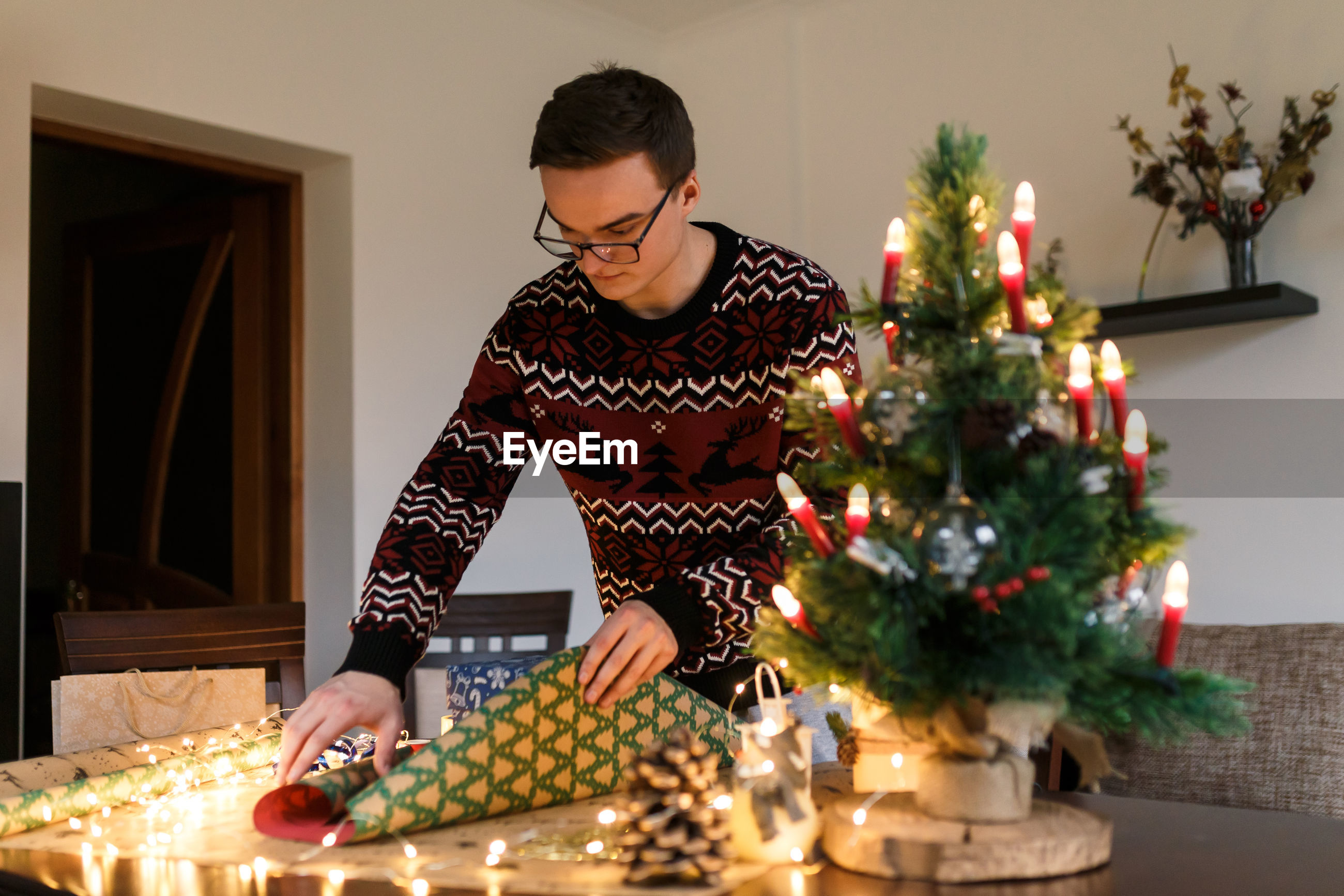 MAN WEARING CHRISTMAS TREE AT HOME