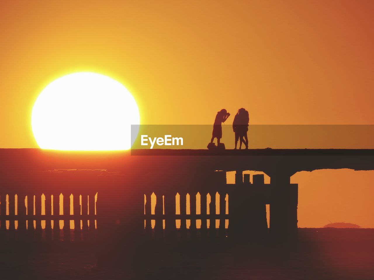 Silhouette People Standing On Pier Over Against Orange Sky