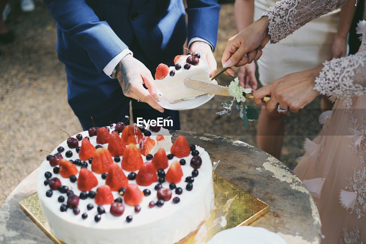 Close-Up Of Hands Cutting Wedding Cake