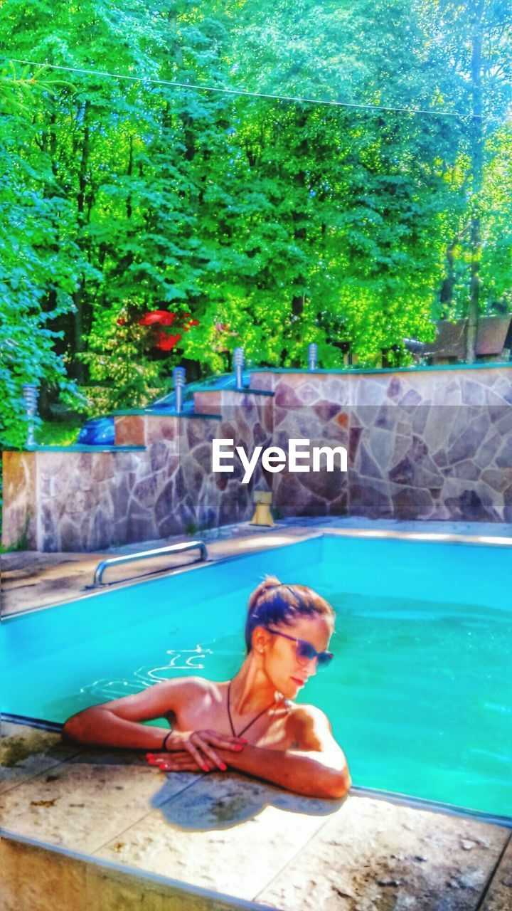 water, swimming pool, day, real people, nature, leisure activity, one person, outdoors, tree, relaxation, lifestyles, beauty in nature, growth, young adult, young women, swimming, waterfall, sitting, full length, flamingo, people