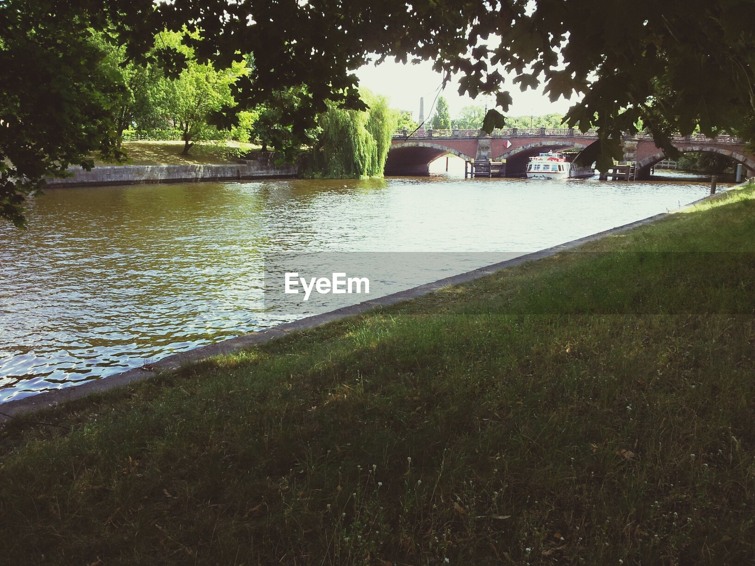 water, grass, tree, built structure, river, park - man made space, architecture, lake, reflection, nature, pond, tranquility, green color, growth, outdoors, day, riverbank, plant, building exterior, no people