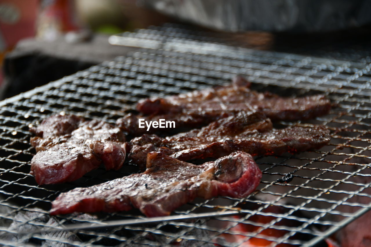 CLOSE-UP OF MEAT ON BARBECUE GRILL IN CONTAINER