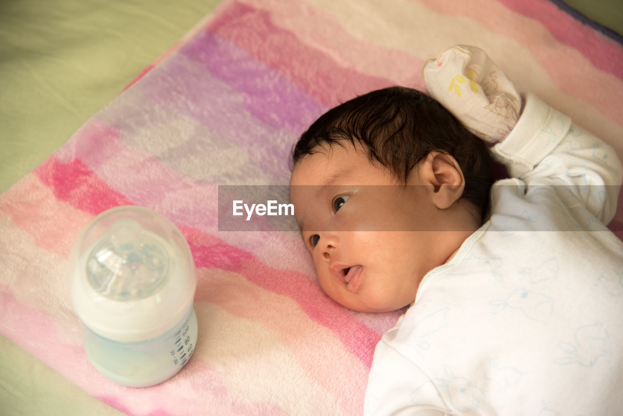 High Angle View Of Baby By Milk Bottle On Bed At Home