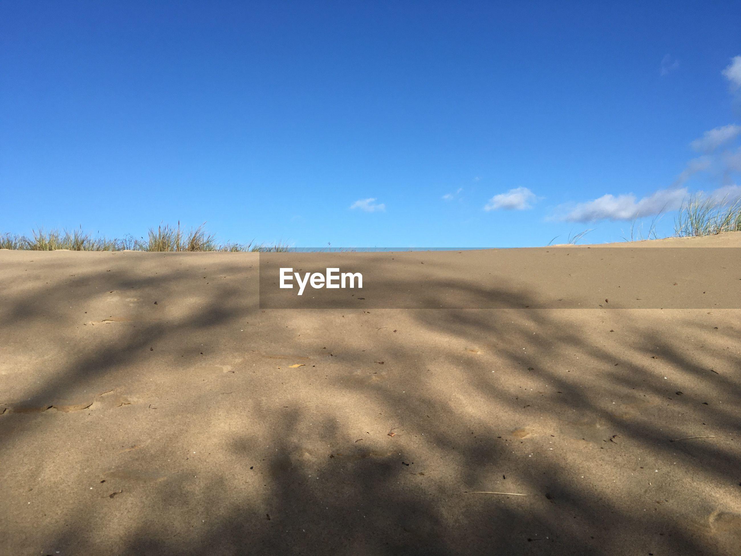 SAND DUNES AGAINST BLUE SKY