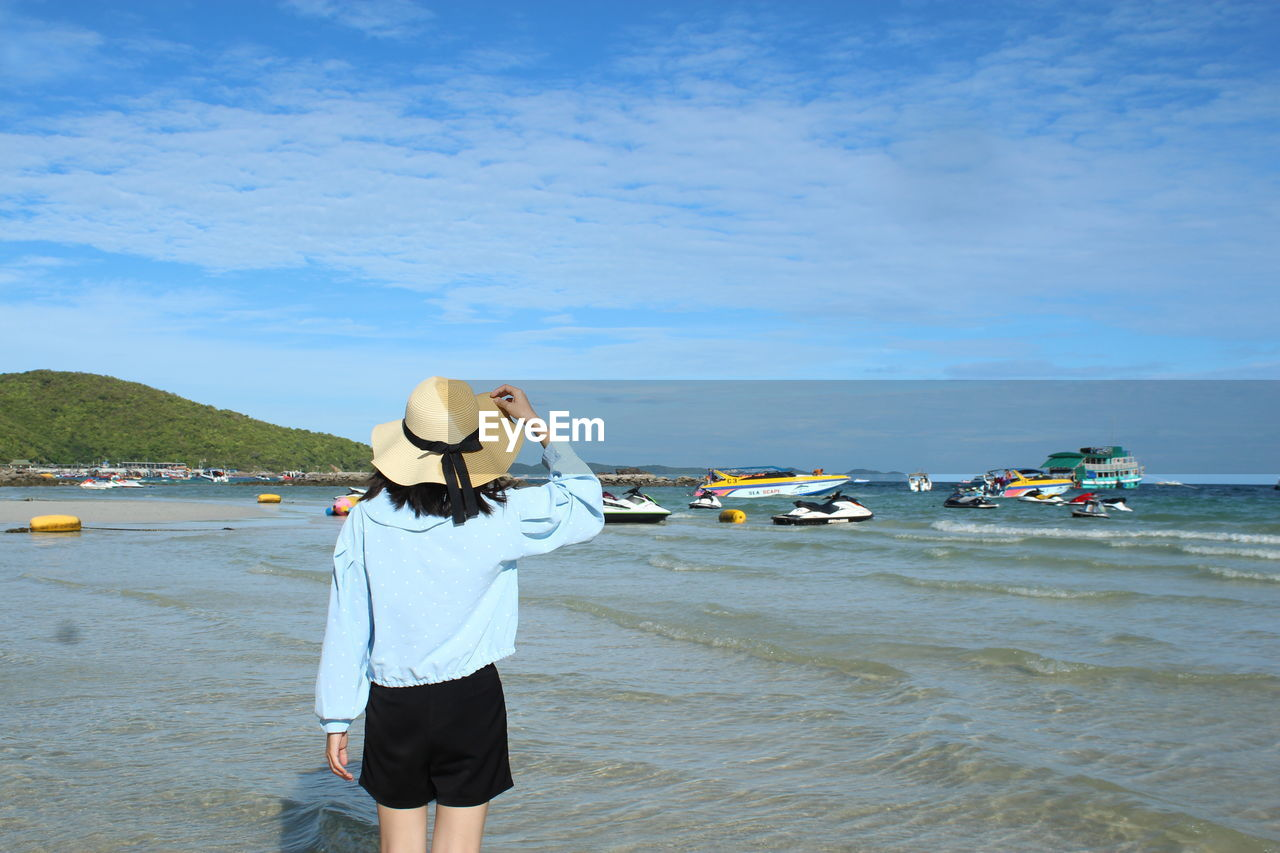 water, sea, real people, lifestyles, sky, one person, rear view, beach, land, leisure activity, standing, three quarter length, nature, hat, day, casual clothing, beauty in nature, incidental people, outdoors