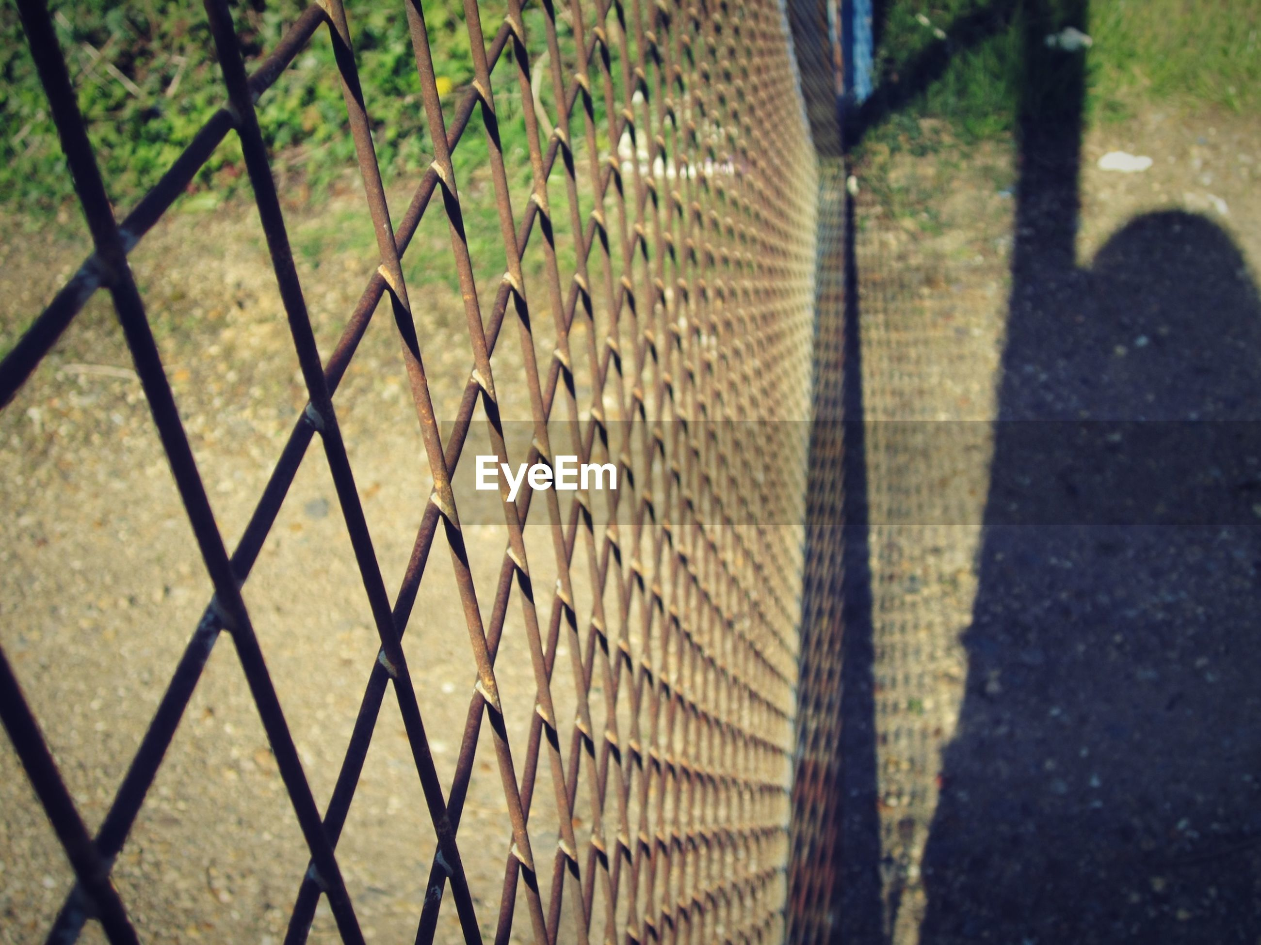 High angle view of chainlink fence with shadow